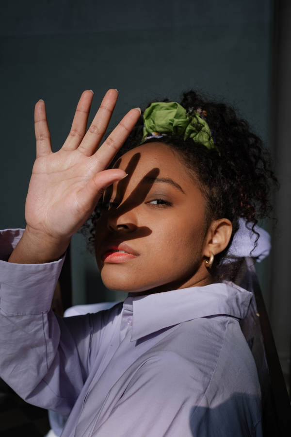 A woman wearing a green scrunchie raising her right palm facing outwards covering the right side of her face, hiding from the sunlight.