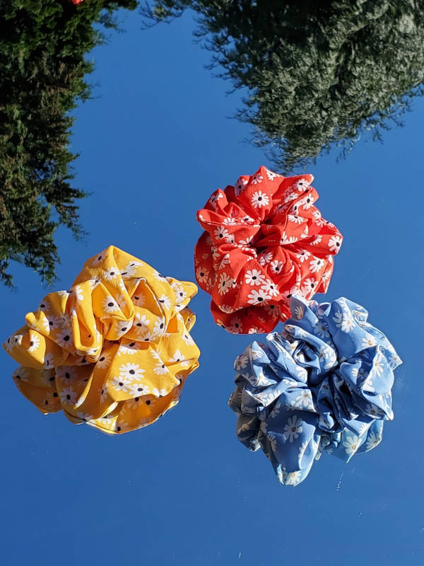 Starting from the left to right, a yellow, red, and blue scrunchie are clad in flower-patterned fabric resting against a clear, blue sky as the image's backdrop.