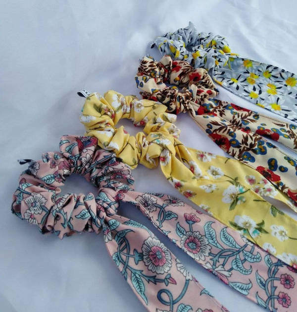 Four pieces of flower-patterned scrunchies sewn with tails resting atop a white cloth.