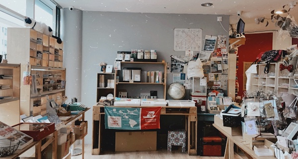 A landscape view of the Stickerrific store inside. Wooden shelves line the walls and art supplies fill the drawers.