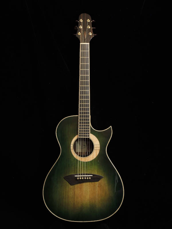 Standing upright, a green durian handmade guitar faces the camera.