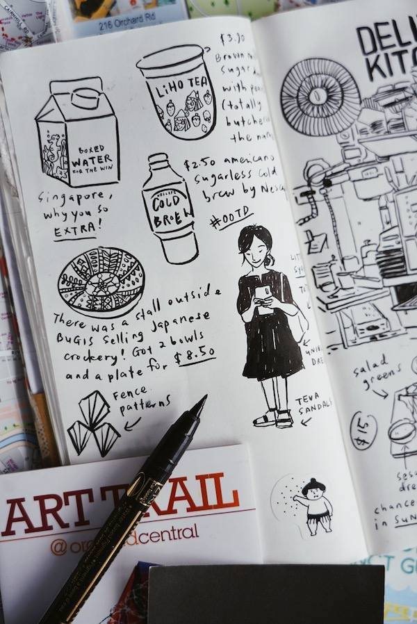 A journal full of drawings and writing next to a black calligraphy pen.