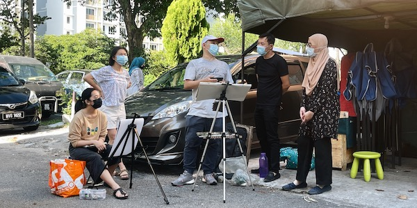 Five people with masks outside painting and talking to each other.