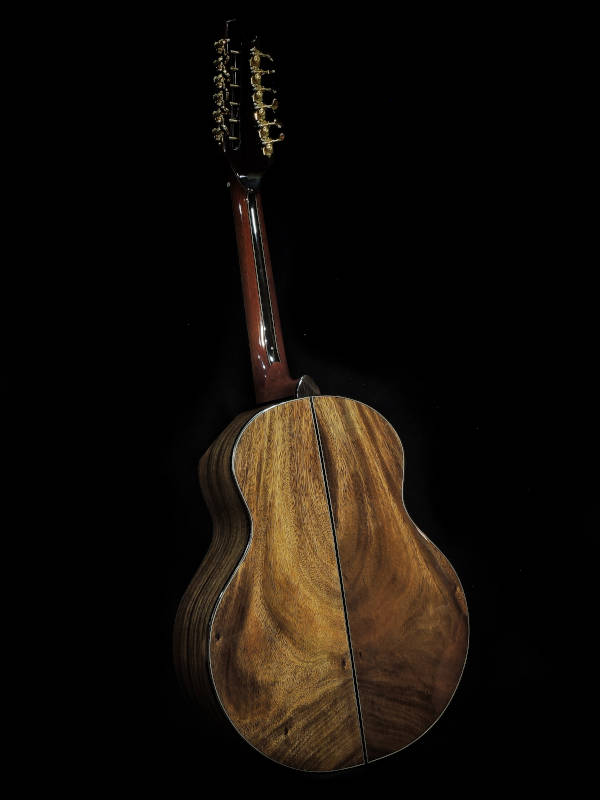 A back view of the handmade Jumbo Mango 12-String Guitar clad in brown-coloured wood with traces of black patterns spread throughout the guitar's back.