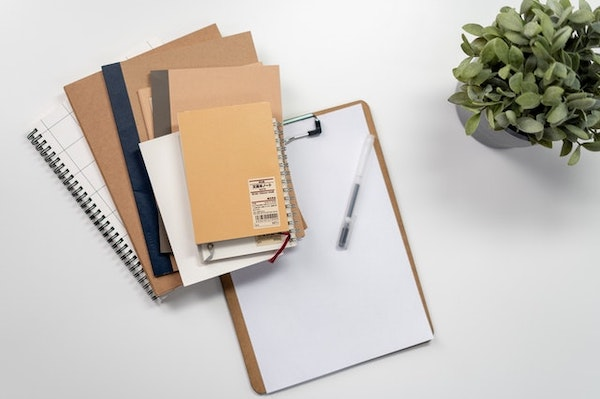 Different types of notebooks arranged on top of each other for note-taking.
