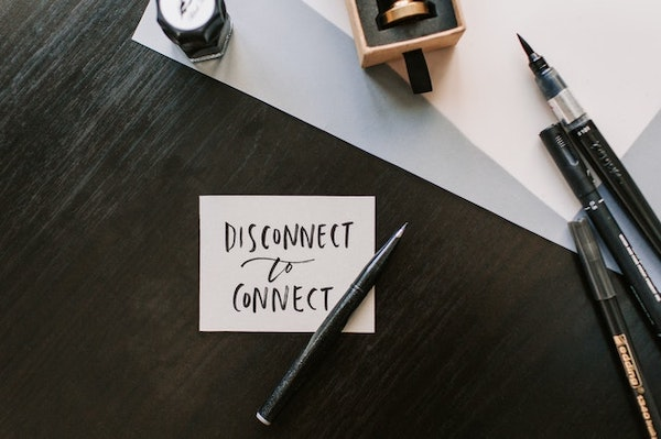 """A Post-it note that writes """"Disconnect to connect"""", next to a bunch of calligraphy pens."""