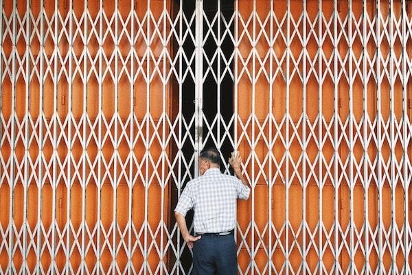 Jia Xin's photo taken at Muar, Johor of an elderly man standing at the doors of a shop lot.
