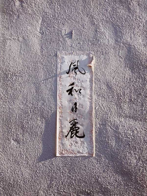 """A picture of a plate on a wall with the words:""""風和日麗"""", which translates into a very warm and lovely day."""