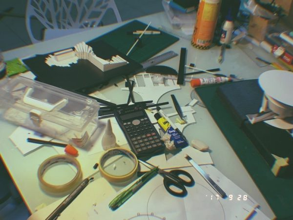 The messy table of an architecture student filled with model making materials.