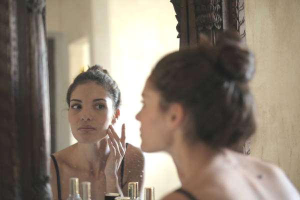 Girl looking at her reflection in the mirror while touching her face with her fingers, examining her cheek.   This image is a glimpse into what having sensitive skin feels like. It can be a really frustrating process.