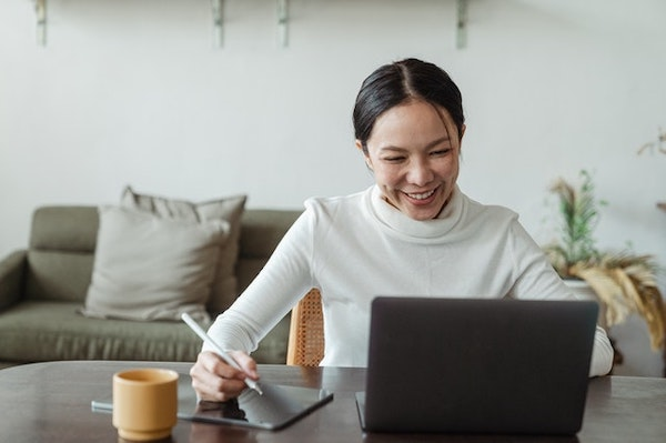 A woman with a smile writing on her tablet while using her laptop.