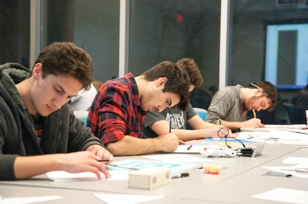 Four students sitting next to each other studying and taking notes utilising different note-taking styles.